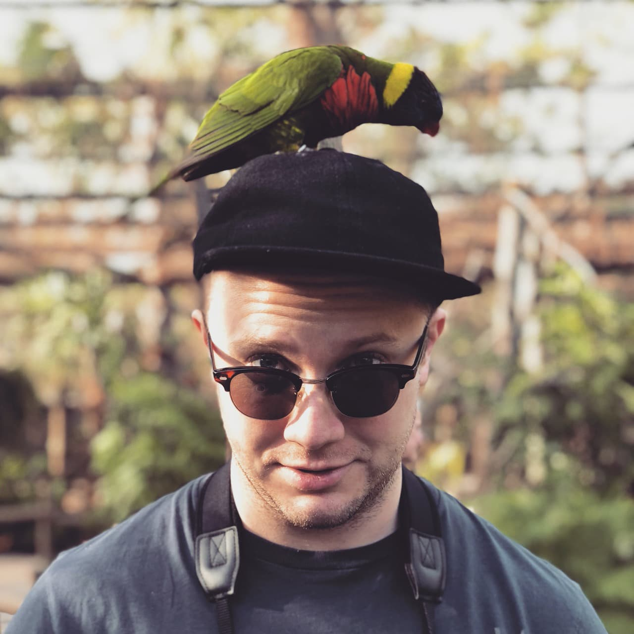 A photograph of Jonathan Clem with a bird poised atop his head